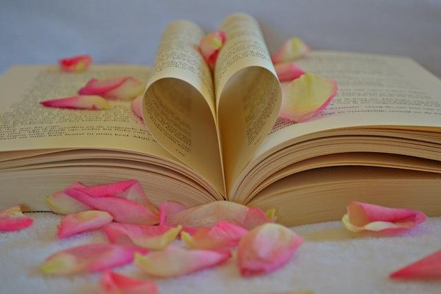 Aufgeschlagenes Buch mit zwei Buchseiten, die so zusammengefaltet sind, dass sie ein Herz formen