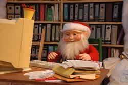 Weihnachtsmann am überladenen Schreibtisch mit Computer auf der Suche nach Geschenken für Autoren